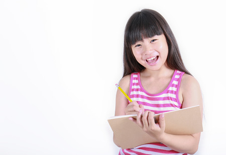 Foto de Young girl writing something with yellow pencil isolated on white, back to school concept - Imagen libre de derechos