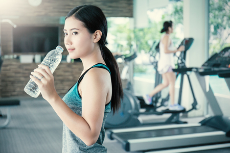 Photo for Asian young woman drinking water after exercise in sport club, asian athlete drinking a bottle of water at the gym. Sport and health care concept - Royalty Free Image
