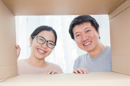 Photo for Asian couple man and woman looking into a cardboard box, Asian man and woman open the cardboard box with surprise expression on their face. - Royalty Free Image