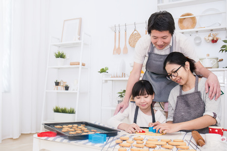 Photo pour Portrait of little asian girl and her parents baking cake and cookies in the kitchen. Happy asian family and mother's day concept - image libre de droit