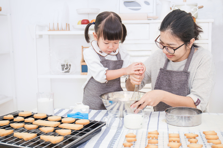 Foto de Little asian girl and her mother baking cake and cookies in the kitchen. Happy family and mother's day concept - Imagen libre de derechos