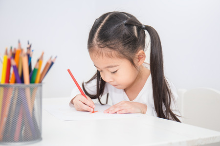 Foto de Education and school concept, little asian student girl drawing with pencils at school - Imagen libre de derechos