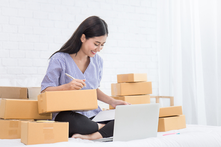 Foto de Start up small business entrepreneur SME or freelance asian typing computer, Young Asian small business owner at home office, online marketing packaging box and delivery, SME concept - Imagen libre de derechos