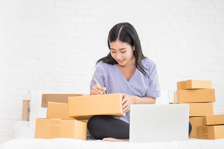 Foto de Start up small business entrepreneur SME or freelance asian woman working with box at home concept, Young Asian small business owner, online marketing packaging box and delivery, SME concept - Imagen libre de derechos