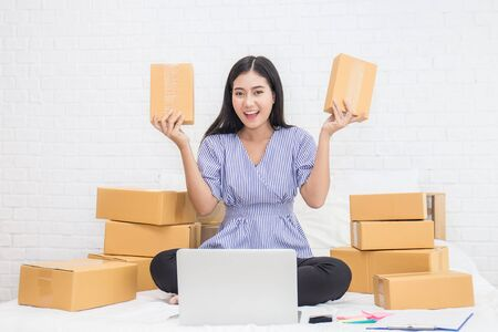 Foto de Start up small business entrepreneur SME or freelance woman holding boxes working at home concept, Young Asian small business owner at home office, on line marketing packaging and delivery, SME concept - Imagen libre de derechos