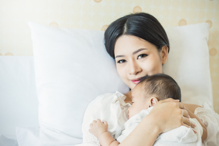 Photo for Close up portrait of beautiful young asian mother with her newborn baby, copy space with bed in the hospital background. Healthcare and medical love, lifestyle concept - Royalty Free Image