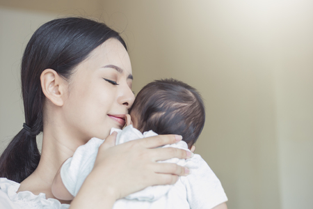 Photo pour Close up portrait of beautiful young asian mother kissing her newborn baby. Healthcare and medical love lifestyle mother's day concept - image libre de droit