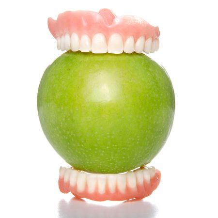 False teeth having a big bite into a green apple
