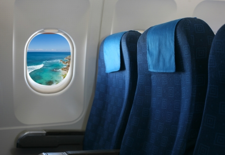 Airplane seat and window inside an aircraft with view on sea and coast in Uluwatu in Bali