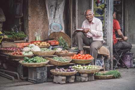 Photo pour MUMBAI, INDIA - 17 JANUARY 2015: Elderly Indian businessman waits for customers in front of grocery store in market street. - image libre de droit