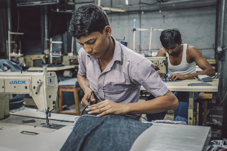 Photo pour MUMBAI, INDIA - 12 JANUARY 2015: Indian workers sew in clothing factory in Dharavi slum. Post-processed with grain, texture and colour effect. - image libre de droit
