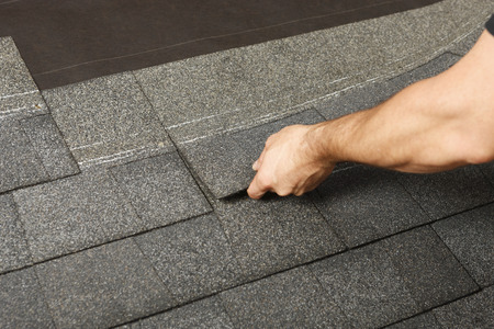 Photo pour Applying roof shingles - image libre de droit