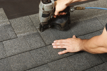 Photo pour Applying roof shingles with a roofing gun - image libre de droit