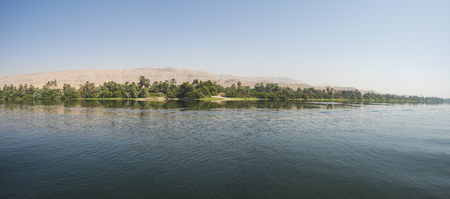 Photo pour Panoramic view across large wide river Nile in Egypt through rural countryside landscape and mountain background - image libre de droit
