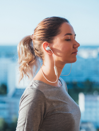 Photo pour Wireless headphones in ears of young woman. - image libre de droit