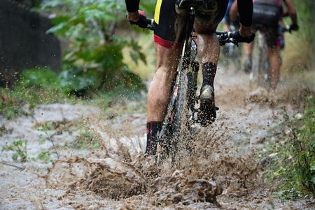 Photo pour Mountain bikers driving in rain upstream creek - image libre de droit