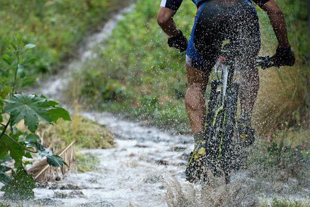 Foto de Mountain biker driving in rain upstream creek - Imagen libre de derechos