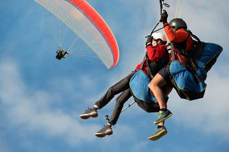 Photo pour Two paraglider tandem fly against the blue sky,tandem paragliding guided by a pilot - image libre de droit