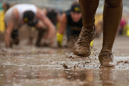 Foto de Mud race runners passing under a barbed wire obstacles during extreme obstacle race,detail of the legs - Imagen libre de derechos