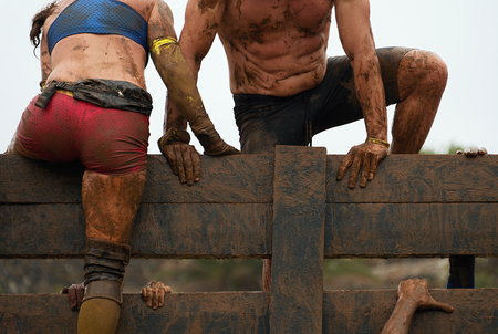 Photo for Mud race runners participants overcome obstacles - Royalty Free Image
