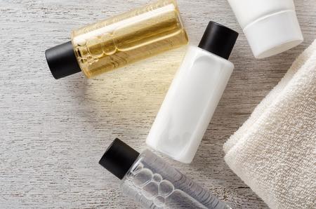 Foto de Shampoo and shower gel with towel on a table - Imagen libre de derechos