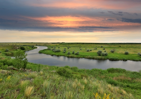 Landscape with river in steppe before rain on sunset