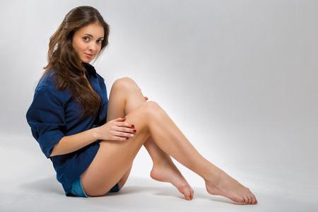 Photo pour Portrait of a beautiful young woman with long slender legs. Photo on a gray background - image libre de droit