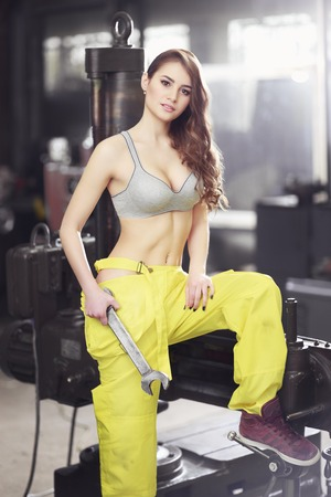 Photo for Nice sexy woman mechanic holding wrench. Girl weared in yellow work overalls and grey uplift standing over the factory - Royalty Free Image