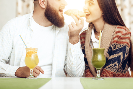 Foto de Portrait of a happy young couple in a restaurant. A happy couple in love with a man and a woman eat a croissant one for two. Romantic date in a restaurant with delicious alcoholic cocktails - Imagen libre de derechos