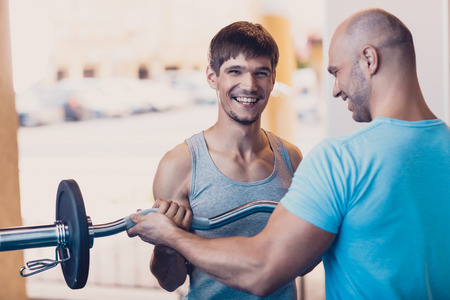 Photo for Trainer controls the physical exercise of the man. A man performs an exercise with barbell standing under the guidance of coach. Exercise with a barbell on the strength of the hands. Sports equipment - Royalty Free Image