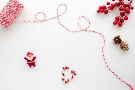 Foto de Christmas composition. Christmas Ribbon, holly berry, candy cane, santa claus, and pine cone. Creative flat lay, top view design - Imagen libre de derechos