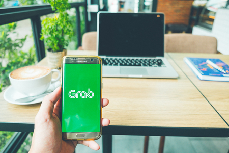 Photo pour CHIANG MAI, THAILAND - June 26,2018: A Man holds Samsung Galaxy S7 edge Mobile Phone with Grab application on the screen in coffee shop. Grab is a ride sharing and logistics services - image libre de droit