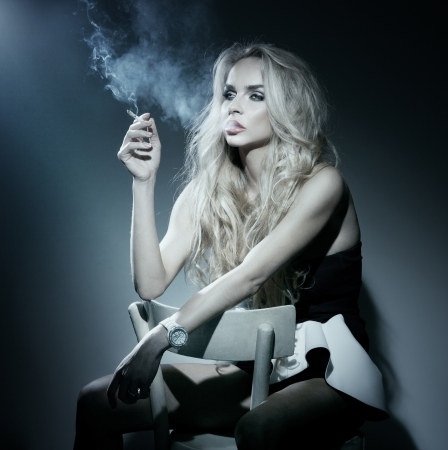Beautiful young blonde woman smoking a cigarette, thinking. Looking away.