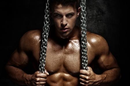 Foto de Handsome young man posing with metal chain. Perfect body. - Imagen libre de derechos