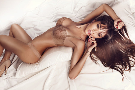 Photo pour Sexy slim brunette woman posing in bed, looking at camera  Lady wearing sensual lingerie  - image libre de droit