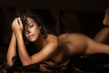 Foto de Beautiful sexy brunette woman lying naked, looking at camera. Girl with perfect body. - Imagen libre de derechos