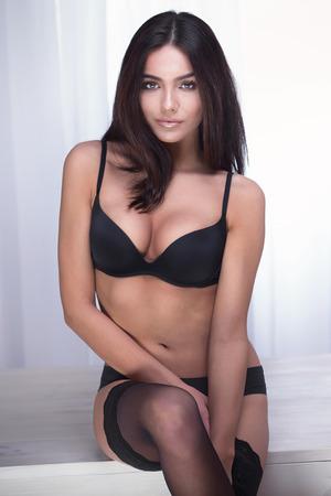 Foto de Sensual beauty posing in black lingerie. Studio shot. Elegant beautiful woman in sexy underwear. - Imagen libre de derechos
