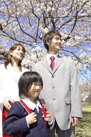Elementary school girls and their parents standing in front of cherry blossoms