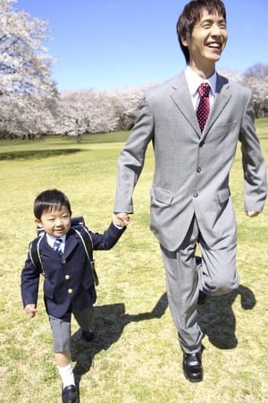 Elementary school boys and father walking hand in hand