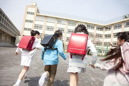 Foto de Rear View of four elementary school students to school - Imagen libre de derechos