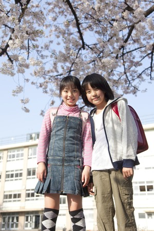 Two elementary school students standing under the cherry tree