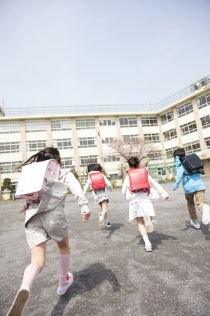 Photo pour Rear View of four elementary school students to school - image libre de droit