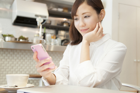 Photo pour Women who operate the smart phone in a cafe - image libre de droit