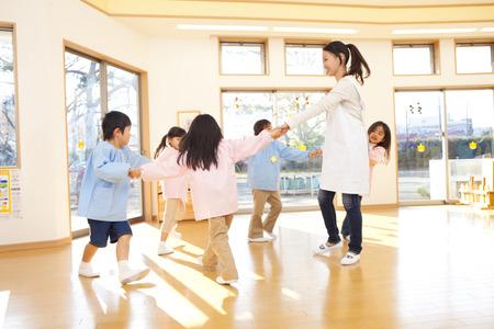 Foto de Kindergarten teachers and kindergarten children dancing in a circle - Imagen libre de derechos