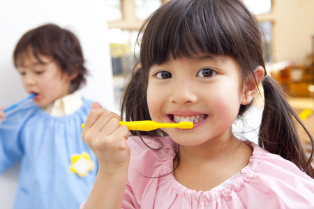 Photo pour Tooth brushing to kindergarten children - image libre de droit