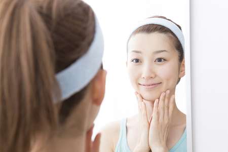 Woman to check your skin in the mirror