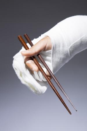 Hands bandaged with chopsticks