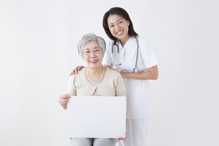 Nurse and senior woman smiling with a message board