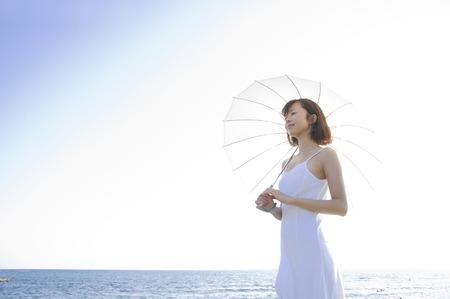 Foto de Woman pointing to a parasol on the beach - Imagen libre de derechos