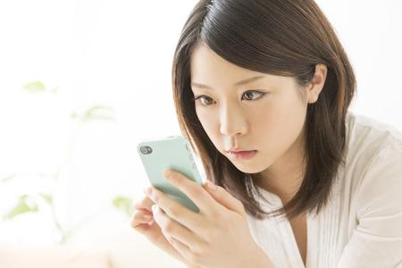 Photo pour Women stare smartphone - image libre de droit
